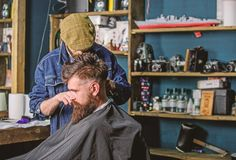 Hipster client getting haircut. Barber with hair clipper works on haircut of bearded guy barbershop background. Hipster. Hairstyle concept. Barber with clipper stock image