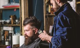 Hipster client getting haircut. Barber with hair clipper works on haircut of bearded guy, retro barbershop background. Barber with clipper trimming hair on stock image