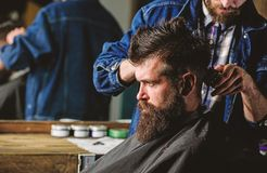 Hipster client getting haircut. Barber styling hair of bearded client with comb and clipper. Barber with hair clipper. Works on hairstyle for men with beard royalty free stock images