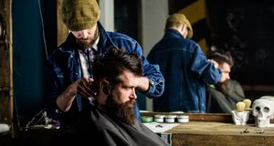 Hipster client getting haircut. Barber styling hair of bearded client with comb and clipper. Haircut concept. Barber. With hair clipper works on hairstyle for royalty free stock photography