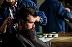 Hipster client getting haircut. Barber styling hair of bearded client with comb and clipper. Barber with hair clipper. Works on hairstyle for men with beard stock photography