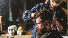Hipster client getting haircut. Barber styling hair of brutal bearded client with clipper. Barber with hair clipper. Works on hairstyle for men with beard stock photos