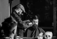 Hipster client getting haircut. Haircut concept. Barber styling hair of brutal bearded client with clipper. Barber with. Hair clipper works on hairstyle for men stock images