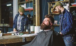 Hipster client getting haircut. Man with beard covered with black cape waiting while barber changing clipper grade. Client with beard ready for trimming or royalty free stock images