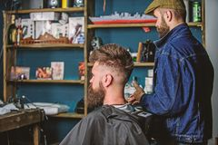 Hipster client got new haircut. Barber with bearded man looking at mirror, barbershop background. Haircut concept royalty free stock photography