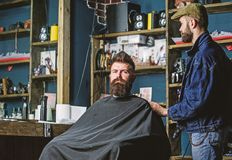 Hipster client got new haircut. Barber with hair clipper looking at mirror, barbershop background. Haircut concept. Professional master checking result while royalty free stock photos