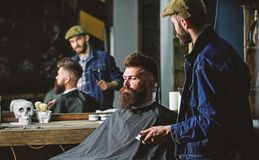 Hipster client got new haircut. Barber with hair clipper looking at mirror, barbershop background. Professional master. Checking result while client sits in stock photos