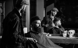 Hipster client got new haircut. Barber with hair clipper looking at mirror, barbershop background. Professional master. Checking result while client sits in royalty free stock images