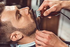 Hipster client visiting barber shop. The hands of young barber making the cut of beard Stock Image