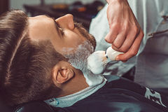 Hipster client visiting barber shop. The hands of young barber making the cut of beard Stock Images