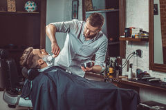 Hipster client visiting barber shop. The hands of young barber making the cut of beard Stock Photography