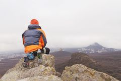 Hipster - a climber in a down jacket and a knitted cap sits and rests on the top of a rock Royalty Free Stock Photography