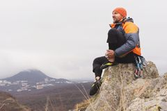 Hipster - a climber in a down jacket and a knitted cap sits and rests on the top of a rock Stock Image