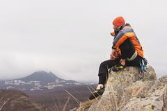 Hipster - a climber in a down jacket and a knitted cap sits and rests on the top of a rock Royalty Free Stock Photos
