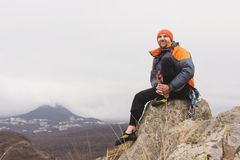 Hipster - a climber in a down jacket and a knitted cap sits and rests on the top of a rock Stock Photography