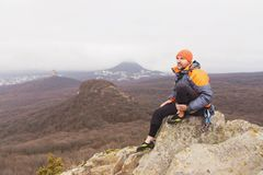 Hipster - a climber in a down jacket and a knitted cap sits and rests on the top of a rock Stock Photos