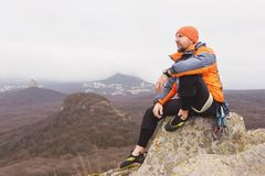 Hipster - a climber in a down jacket and a knitted cap sits and rests on the top of a rock Royalty Free Stock Image
