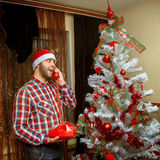 Hipster congratulates phone Merry Christmas and a happy new year Stock Photos