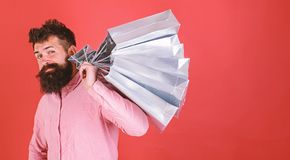Hipster on cool face is shopping addicted or shopaholic. Guy shopping on sales season with discounts. Shopping concept. Man with beard and mustache carries royalty free stock image