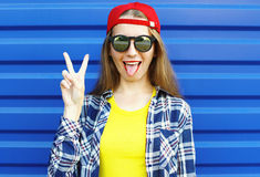 Hipster cool girl in sunglasses and colorful clothes having fun. Fashion hipster cool girl in sunglasses and colorful clothes having fun over blue background Stock Photography