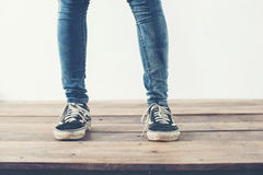 hipster cool woman feet with black sneakers, soft vintage toned Royalty Free Stock Image