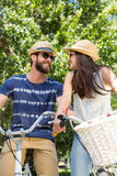 Hipster couple on a bike ride in the park Stock Photography