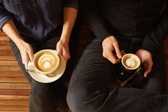 Hipster couple with cappucino and espresso from overhead Royalty Free Stock Photo
