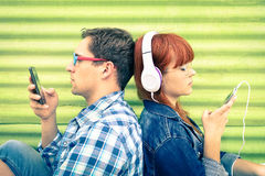 Hipster couple in disinterest moment with mobile smart phones. Hipster couple in disinterest moment with mobile phones - Concept of apathy sadness and isolation Royalty Free Stock Images