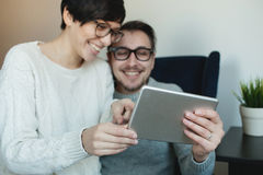 Hipster couple in eyewear enjoying the tablet together Royalty Free Stock Photography