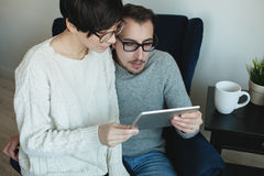 Hipster couple in eyewear enjoying the tablet together Stock Photo