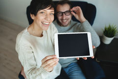 Hipster couple in eyewear showing the screen of tablet Royalty Free Stock Images