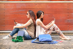 Hipster couple of girlfriends in disinterest moment with phones. Hipster couple of girlfriends in disinterest moment with mobile smart phones - Concept of royalty free stock photography