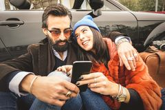 Hipster couple having fun with mobile smart phone at car roadtrip - Friendship concept with best friends connecting and sharing. Content on social media stock image