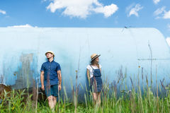 Hipster couple hiding faces behind a hats. Playing outdoors on a beautiful sunny summer day Stock Photography