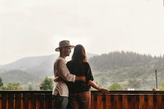 Hipster couple hugging on porch of wooden house looking at mount Royalty Free Stock Photos