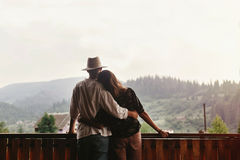 Hipster couple hugging on porch of wooden house looking at mount Royalty Free Stock Images
