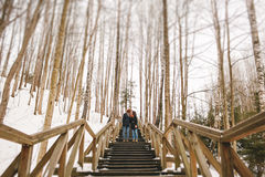 Hipster couple kissing on wooden stairs in winter park Stock Photos