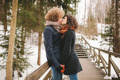 Hipster couple kissing on wooden stairs in winter park Stock Photo
