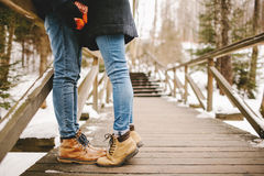Hipster couple kissing on wooden stairs in winter park Royalty Free Stock Photography