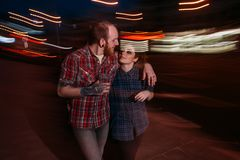 Hipster couple in motion. Youth nightlife. Romantic date outdoors, blurred lights urban background, hugging young people, love concept Stock Image