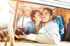 Hipster couple ready for roadtrip on oldtimer mini van transport. Travel lifetstyle concept with indie people kissing on minivan adventure trip having fun Royalty Free Stock Images