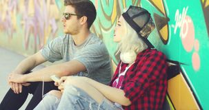 Hipster couple relaxing against a graffiti wall. Young hipster couple relaxing against a colorful graffiti covered wall sitting on the sidewalk pointing and stock footage