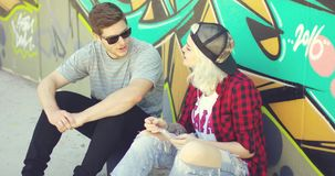 Hipster couple relaxing against a graffiti wall stock footage