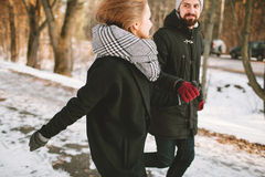 Hipster couple running in winter park looking at each other Stock Images