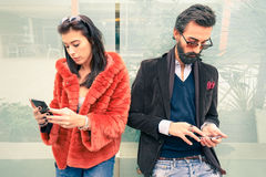 Hipster couple in sad moment ignoring each other using smartphone. Hipster couple in sad moment ignoring each other using mobile phones - Concept of apathy Stock Images
