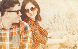 Hipster couple, with sunlight effect. Happy hipster couple in love is sitting on hay. Low contrast, with sunlight effect Stock Image