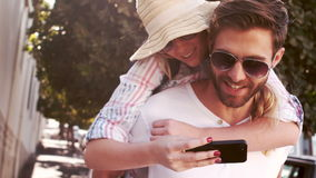 Hipster couple taking selfie while doing piggy back stock video footage