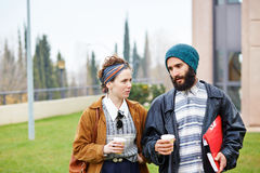Hipster couple talking and drinking coffee to go Stock Images