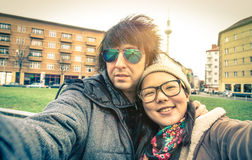 Hipster couple of tourists taking a selfie in Berlin City. Multiracial concept of friendship and fun with new trends and technology - Asian girl with Stock Images