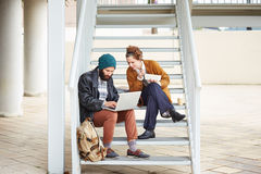 Hipster couple using computer and eating lunch outdoors Stock Photo